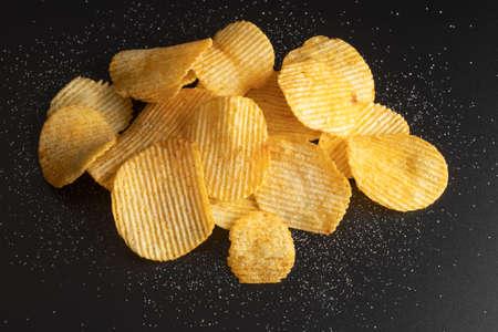 Photo pour Heap of crispy potato chips on black background - image libre de droit