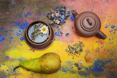 Herbal and floral tea. Still life- cup, kettle and pear for dessert. Background- white plaster on the wall. It is possible to print large format.