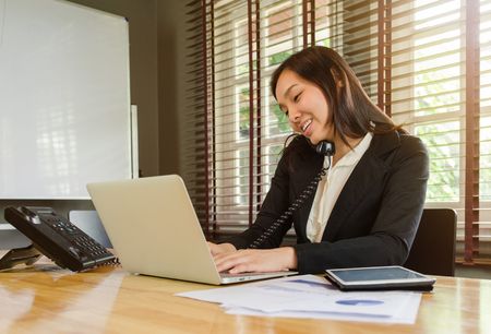 woman working in office and talking telephone