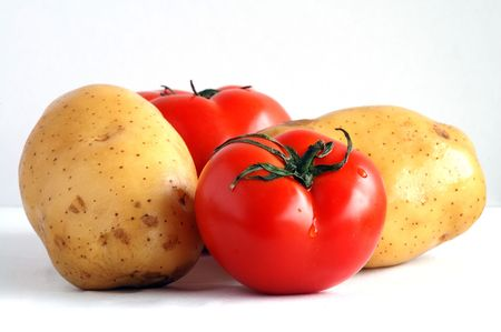 Two potatoes and two fresh tomatoes together