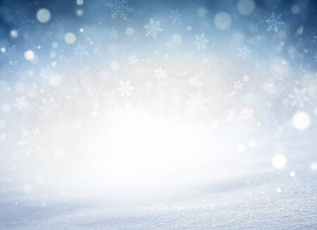 Snowflakes and snowfall on a cold blue winter background and a powder snow ground. Winter seasonal material.