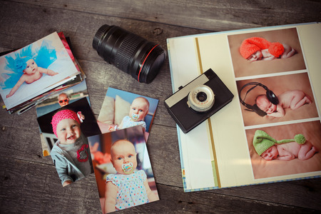 Foto de Album with children is photos, the ancient camera and a lens on a wooden background - Imagen libre de derechos