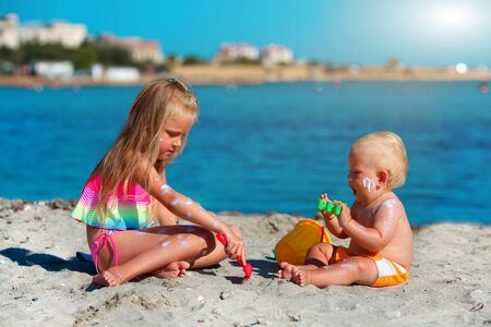 Photo for Children play on the beach. Summer water fun for the family. Boy and girl with toy buckets and a shovel on the seashore. Sunscreen applied to children is skin - Royalty Free Image