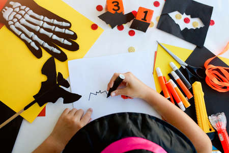 Photo pour Little girl in a witch costume draw a bat, for the holiday of halloween on a light table. Halloween decor. Handicraft. The concept for Halloween. DIY. - image libre de droit