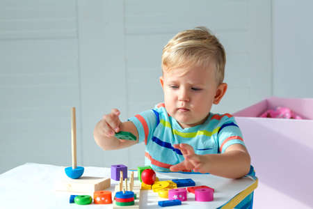 Photo for Little boy 2 years old is played with a wooden pyramid. Educational logic toys for children. Montessori games for child development. Copy space. - Royalty Free Image