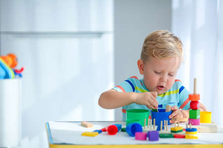 Photo for Little boy 2 years old is played with a colors toys. Educational logic toys for children. Montessori games for child development. Copy space. - Royalty Free Image