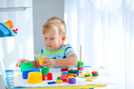 Photo pour Little boy 2 years old is played with a colors toys. Educational logic toys for children. Montessori games for child development. Copy space. - image libre de droit