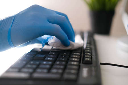 Photo for Male hands in rubber gloves wipe the keyboard from the computer. Disinfection in the office during COVID-19 - Royalty Free Image