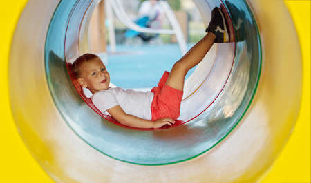 Photo pour A little boy enjoys the underground multicolored tube on the playground on a sunny summer day. - image libre de droit