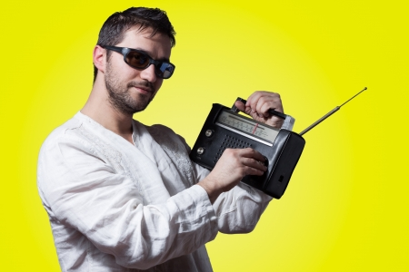 Young bearded man holding a vintage radio on yellow background