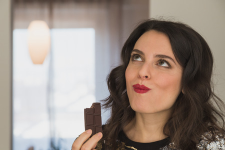 Photo pour Beautiful young brunette with long hair eating chocolate at home - image libre de droit