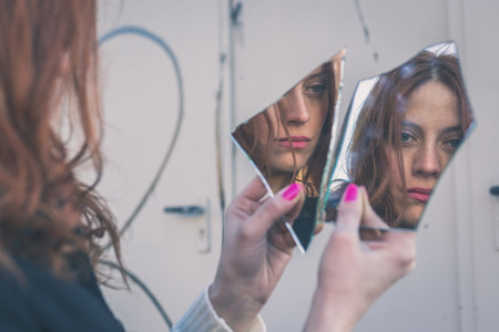 Photo pour Beautiful redhead girl with long hair and blue eyes looking at herself in a broken mirror - image libre de droit