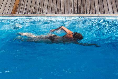 Photo pour Top view of a  woman in bikini swimming in a  pool - image libre de droit