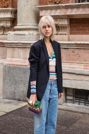 MILAN, ITALY - JUNE 19: Fashionable woman poses outside Missoni fashion show building during Milan Men's Fashion Week on JUNE 19, 2016 in Milan.
