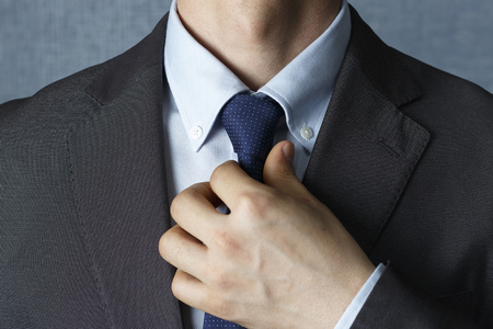 Photo for Man in suit straightens tie close up, front view - Royalty Free Image