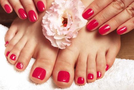 Foto de Pink manicure and pedicure with flower close up on a white background, top view - Imagen libre de derechos