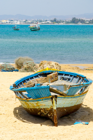 Old fishing boat on the beach of the Mediterranean Sea at Hammamet in Tunisia