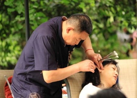 Chengdu China - May 04,2012 ,Chinese man cleanining ear wax for his customer,Ear wax cleaning business, in Peoples s Park in Chengdu China