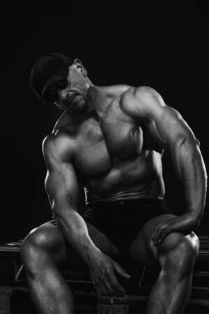 Photo for Black and white portrait of a seated man of perfect physique in shorts and a baseball cap. - Royalty Free Image