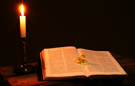 bible or spiritual  book and candle, religious scripture lit by flame
