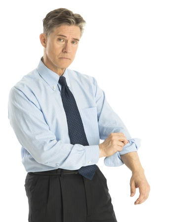 Portrait of tired mature businessman rolling up his sleeves while standing isolated over white background