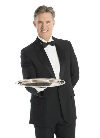 Portrait of happy waiter carrying serving tray while standing isolated over white background