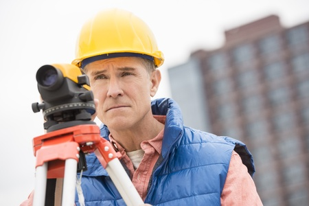 Confident mature construction worker with theodolite looking away while at standing construction site