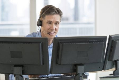 Happy mature male customer service representative using multiple screens at desk in office