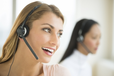 Close-up of happy female customer service representative looking away with colleague in background