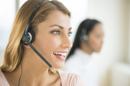Happy female customer service representative looking away with colleague in background