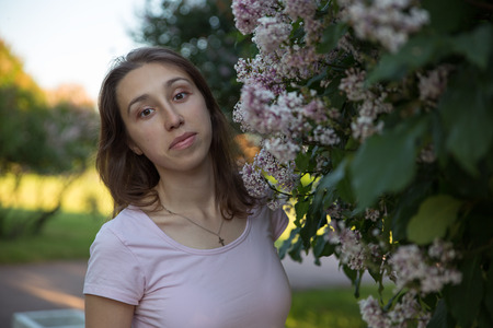 Photo for Beautiful Russian girl under lilac flowering trees - Royalty Free Image