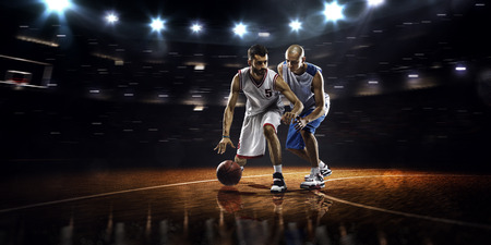 Two basketball players in action in gym in lights