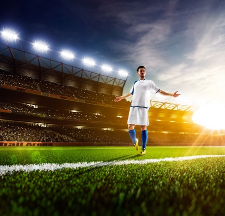 Soccer player in action on sunny stadium panorama background