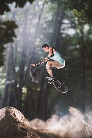 bmx bicycle rider tricking on the forest hills