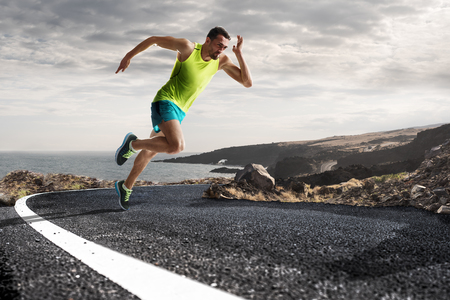 Foto de Running athlete man. Male runner sprinting during outdoors training for marathon run. Athletic fit young sport fitness model in his twenties in full body length on road outside in nature. - Imagen libre de derechos