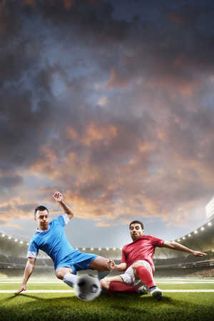 Soccer players in action on sunset stadium background panoramaの写真素材