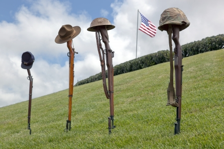Vintage riflles and soldier's hats and helmets forming Fallen Soldier Battle Crosses, American Flag behind.