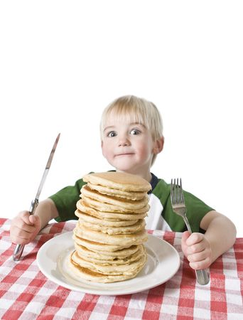 Little boy with a giant plate of pancakes, a knife and fork on a table cloth. Shallow DOF with focus on the pancakes.