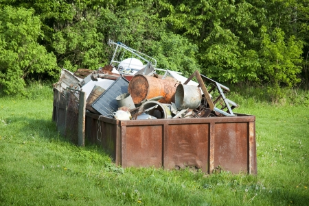 Rusty waste container full of scrap metal
