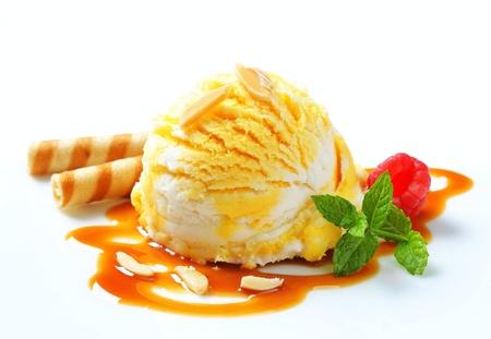 Scoop of yellow white ice cream with caramel sauce