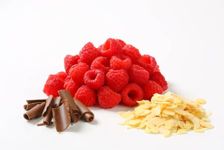 Heaps of fresh raspberries, chocolate curls and sliced almonds
