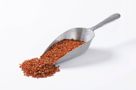 Scoop of uncooked red rice