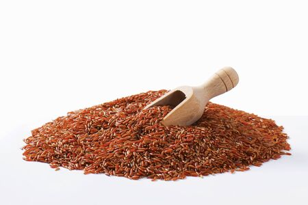 Heap of Camargue red rice and wooden scoop