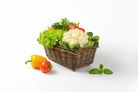 basket of fresh vegetables on white backgroundの写真素材