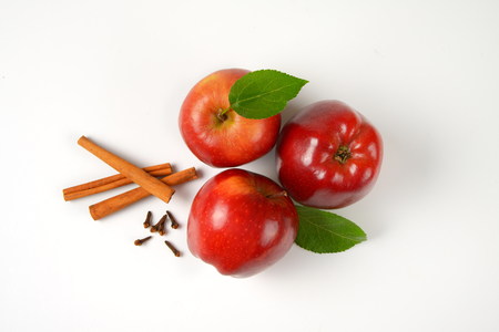 Photo for three red apples, cinnamon sticks and dried cloves on white background - Royalty Free Image