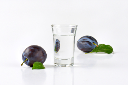 Shot of plum brandy (slivovitz) and fresh damson plums next to it