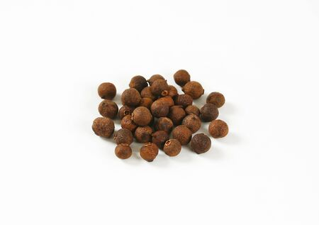pile of allspice berries on white background