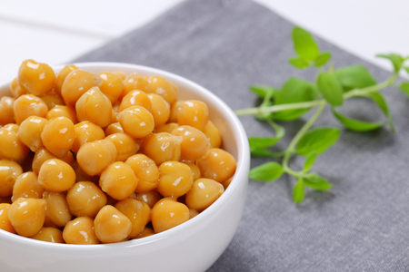 bowl of cooked chickpeas on grey place mat - close up