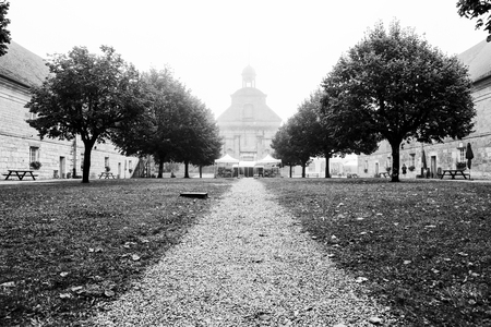 Foggy autumn pathway leading to a majestic cathedral