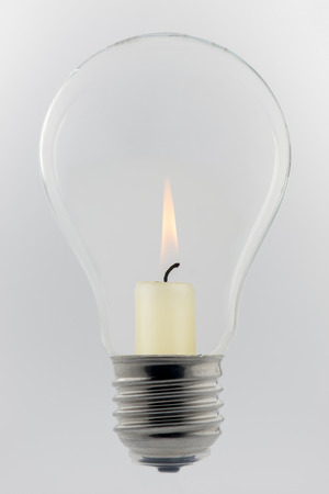 Conceptual glass light bulb with burning candle inside